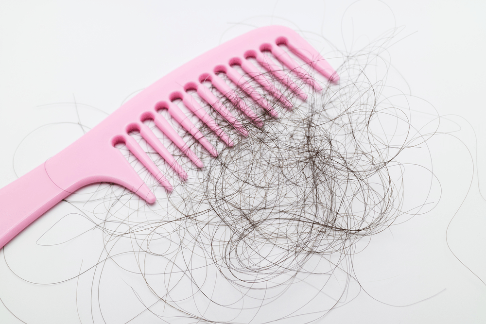 Pink comb with lots of hair fall